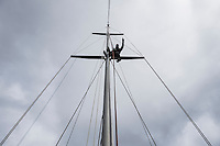 Man sitting on sailboat mast points into distance