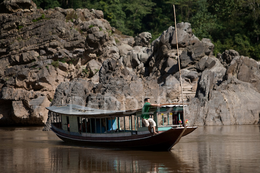 A man works on his wooden river boat along the Mekong River in Laos.