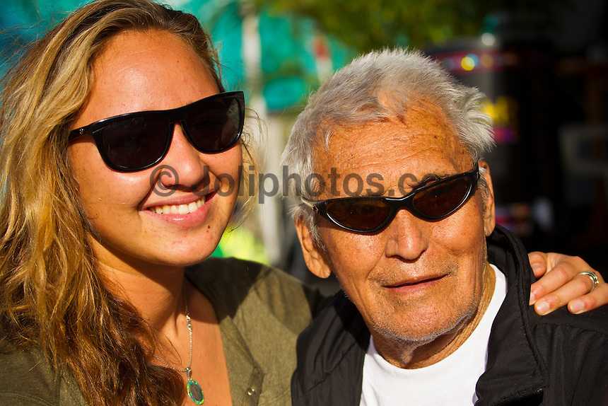 HONOLULU/Oahu/Hawaii.(Nov. 28, 2011)  Carissa Moore (HAW) with Beach Marshal, 92 year old former Waikiki Beach Boy Rabbit Kekai (HAW). -- The $250,000 Vans World Cup of Surfing continued today  in shifting 5- to 8 -foot surf at Sunset Beach on Oahu's North Shore. Waves were in the mid size range for most of the day with strong side shore Trade winds. The Vans World Cup is the second leg of the 29th annual Vans Triple Crown of Surfing, presented by Rockstar Energy Drink.. Photo: joliphotos.com