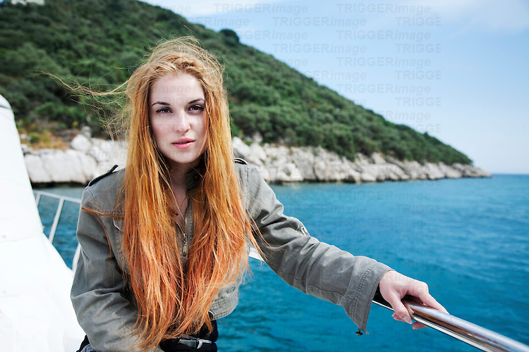 Strawberry blonde girl sitting in a boat with an island and water scenery behind her