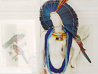 A colourful African headdress and beads adorn a marble statue in the entrance hall