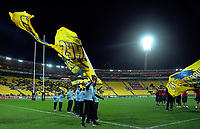 Flag-bearers battle the wind before the Super Rugby match between the Hurricanes and Chiefs at Westpac Stadium in Wellington, New Zealand on Friday, 27 April 2019. Photo: Dave Lintott / lintottphoto.co.nz