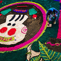 A Mexican boy creates a colorful sawdust carpet, displaying La Calavera icon, during the celebrations of the Day of the Dead (Día de Muertos) in Tláhuac, Mexico, 31 October 2016.