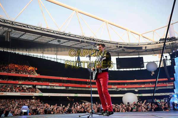 Matt Bellamy of Muse.Muse perform live in concert, Emirates Stadium, London, England, UK,.25th May 2013..music gig on stage performance performing full length red trousers playing guitar singing on toes jumping  microphone black white top jacket .CAP/MAR.© Martin Harris/Capital Pictures.