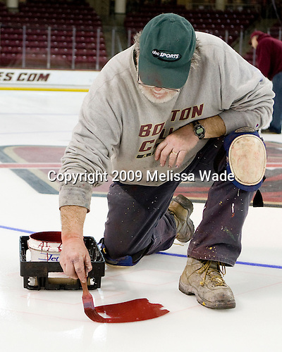 Paul Gallivan starts the painting with number 6 (Tim Kunes).  The maroon is a custom color purchased by BC.  Paul Gallivan and his crew paint the numbers of any senior players and the initials of any senior managers of the men's and women's Boston College hockey teams at center ice prior to the final home game of the regular season.  On the evening of Tuesday, March 3, 2009, they painted the numbers and initials for the men's team after cutting out the women's numbers earlier that day (the women's regular season ends two weeks earlier than the men's.)