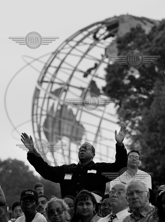 An audience member raises his hands at Christian evangelist Billy Graham's crusade held at Flushing Meadows in New York City.