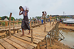 Rohingya refugees cross a rickety foot bridge in the sprawling Kutupalong Refugee Camp near Cox's Bazar, Bangladesh. More than 600,000 Rohingya have fled government-sanctioned violence in Myanmar for safety in Bangladesh.