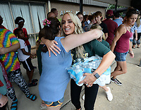 NWA Democrat-Gazette/ANDY SHUPE<br /> Carrie Jernigan (right) receives a hug Saturday, Aug. 10, 2019, as she and her daughter, Harper, 9, hand out bottles of water to residents as they wait outside in the heat during the River Valley Kick Start at Alma Middle School. Inspired by her daughter, Harper, Jernigan bought all 1,500 pairs of shoes from a closing Payless Shoe Source in Fort Smith. Her effort national publicity and thousands of dollars in donations, which she used to buy more shoes and school supplies for kids going back to school.
