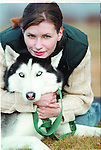 Portrait of healthy, attractive young white woman hugging her dog, Siberian Husky