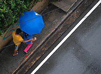 Manila, Philippines Raining and looking down at the street people walking with colourful umbrellas, Manila, Philippines