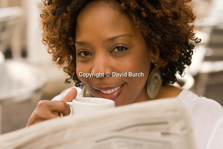 African American woman reading newspaper, drinking coffee