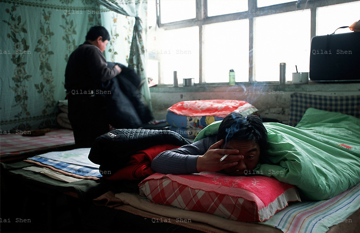 Opera034 20030207 SHANXI, CHINA: Jin Opera actor Jin Rui smokes an cigarett while rubbing the sleep from his eyes at the troupe's temporary residence in a rural village in Shanxi Province, China 07 February 2003.