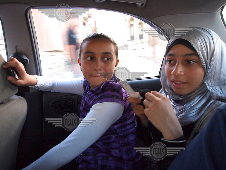 """Amira Al-Qerem (16, second from left) and her sister Haya are driven through Gaza City on October 28 2010. Amira was missing and presumed dead after she was injured by one of the same explosions that killed her father, brother and sister during the last days of the Israeli invasion of Gaza in 2009. She was found three days later, after her family thought they had buried her remains with those of the other three. She is one of the main subjects of the controversial documentary film """"Tears of Gaza"""" by director Vibeke Løkkeberg."""