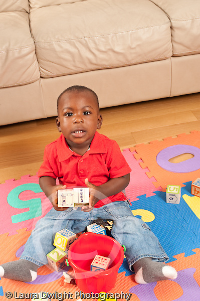 12 month old baby boy holding blocks and looking at camera saying word vertical