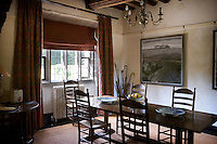 The traditional dining room is graced by a pair of contemporary landscape paintings