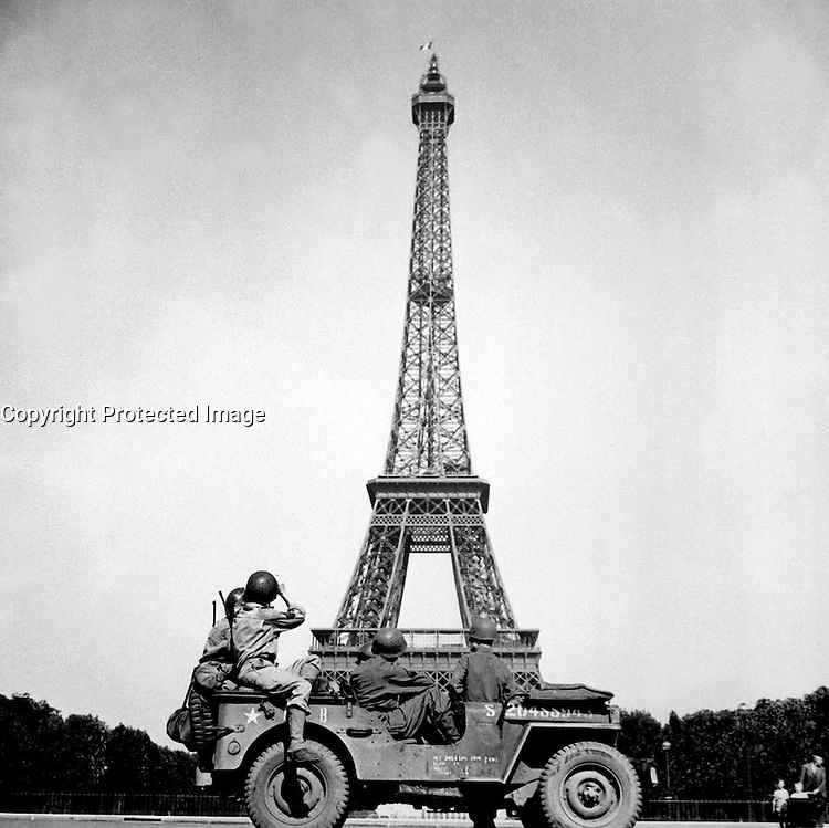 Soldiers of the 4th U.S. Infantry Division look at the Eiffel Tower in Paris, after the French capital had been liberated on August 25, 1944. John Downey. (OWI)