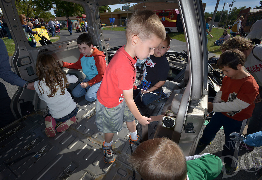 STAFF PHOTO BEN GOFF  @NWABenGoff -- 10/04/14 Children demolish a minivan in the 'Car Take-Apart' during the Amazeum's inaugural Tinkerfest at Old High Middle School in Bentonville on Saturday October 4, 2015. George Nunnally Chevrolet in Bentonville donated the used minivan for children to strip to the frame during the event.