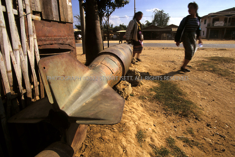 Phonsavan, Laos..Villagers pass a huge American bomb sitting outisde a home...All photographs ©2003 Stuart Isett.All rights reserved.