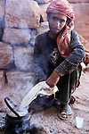 Portrait of Bedouin man making tea in the ancient city of Petra in Jordan. Petra is the most visited tourist attraction in Jordan, a symbol of the country for its historical and archaeological importance. It has been a UNESCO World Heritage Site since 1985. The Bedouin families agreed to move out of the caves and tombs, they have been living for centuries, into a small village, built near the site of Petra. Most of them earn their living from tourism which seems to be the only option available, especially for the younger generations.