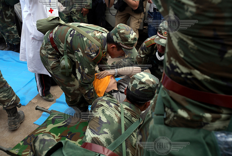 Soldiers move a survivor pulled from the rubble three days after an earthquake measuring 7.9 on the richter scale hit Sichuan.