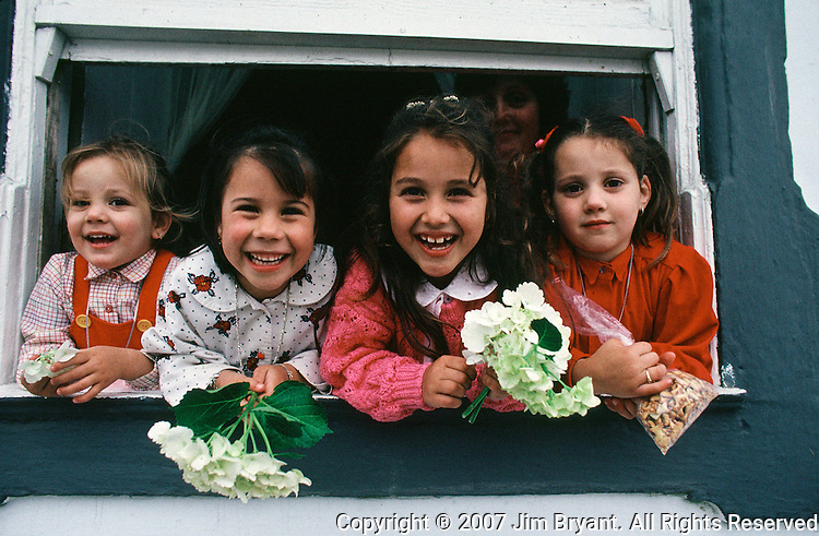 Four girls watch the the Divino Espirito Santo parade from their home on Terceira, Azores. Far out in the Atlantic Ocean, some 850 miles off the western coast of Lisbon, Portugal lies the 425-mile long archipelago of the Azores. (Jim Bryant Photo).....