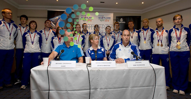 Michael Cavanagh, chairman of Commonwealth Games Scotland, (left) with MSP Shona Robison and Jon Doig, Scottish chef de mission, during the press conference with all the Scottish medalists behind after returning home from the Delhi Commonwealth Games at Glasgow International airport. .Picture: Universal News And Sport (Scotland). 16 October 2010...