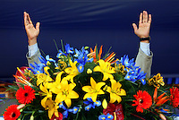 The President of Iran, Mahmoud Ahmadinejad raises his hands from behind a decorative and colourful flower bouquet during a speech in the Iranian city of Kashan. ...