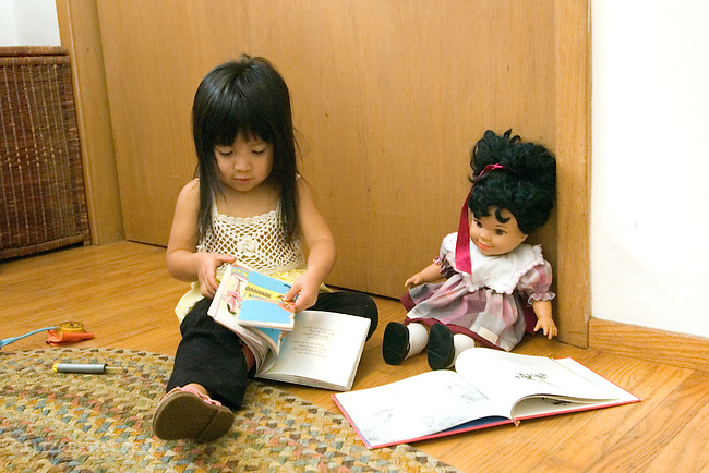 "Berkeley CA Girl, age two and a half, Guatemalan, ""reading"" book to her doll MR"