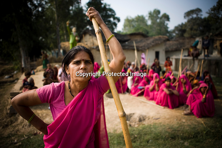 The 47-year-old leader of the Pink Gang, Sampat Pal Devi is seen with the members of the pink gang in the background. A fiesty woman, barely educated, impoverished mother of five, Sampat Pal Devi has emerged as a messianic figure in the region. Sampath Devi began to work as a government health worker, but she quit soon after because her job was not satisfying enough. She always wanted to work for the poor and not for herself. Taking up issues while being a government worker was difficult, so she decided to quit the job and work for the rights of people...Amidst the gloom of extreme poverty, it's the colour of pink that's calling the shots in this dusty region of Bundelkhand, one of the poorest parts of one of India's northern and most populous states, Uttar Pradesh in India. A gang of vigilantes, called the Gulabi Gang (pink gang) - its 10,000 strong women members wear only pink sarees - is taking up lathi (traditional Indian cudgel) against domestic violence and corruption.