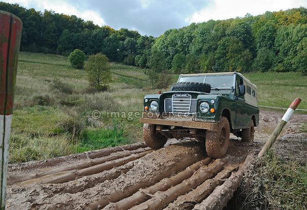 Bronze green 1970s Land Rover Series 3 LWB Softop crossing a small river via a wooden bridge made of tree trunks. Seen at an off-road event of the German Land Rover Club held at the Freizeitpark Mammut in Stadtoldendorf, Germany, October 3.-5. 2008. --- No releases available. Automotive trademarks are the property of the trademark holder, authorization may be needed for some uses.