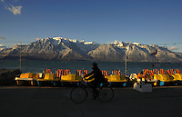 Early morning cyclist riding along promenade with lake side pedaloes overlooking Lake Léman at Vevay, Lausanne, Switzerland.