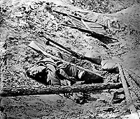 Dead Confederate Soldier in the Trenches.  This photograph was taken April (3), 1865, in the Rebel trenches at Petersburg just after their capture by Union troops.  Attributed to Thomas C. Roche.  Mathew Brady Collection. (Army)<br /> NARA FILE #: 111-B-65<br /> WAR &amp; CONFLICT BOOK #:  256