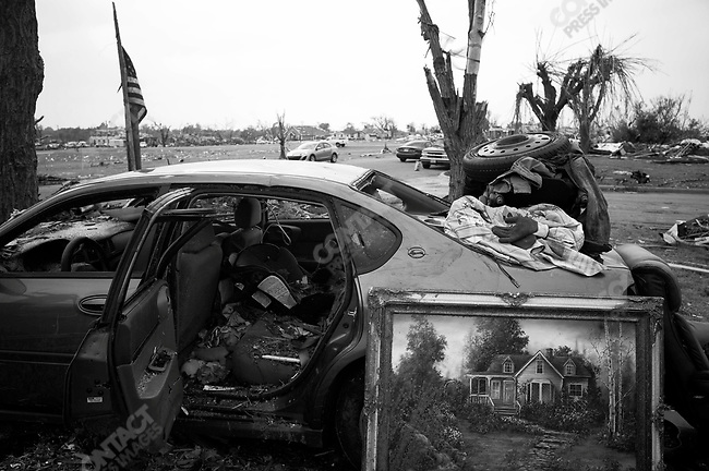 An unscathed oil painting lies next to a wrecked car on front lawn of the Stallsmith family home. Joplin, Mo. May 24, 2011...