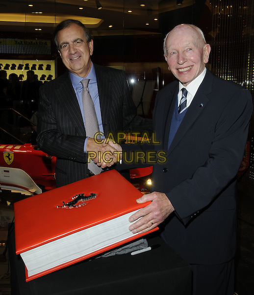H.R. ALAIN GIORGIO MARIA ECONOMIDES,  AMBASSADOR OF ITALY TO THE UK & JOHN SURTEES OBE.At the official Ferrari Opus Launch Party, Ferrari Store, Regent Street, London, England, UK, December 17th 2010..half length suit tie grey gray blue shirt  book pinstripe shaking hands white black .CAP/CAN.©Can Nguyen/Capital Pictures.