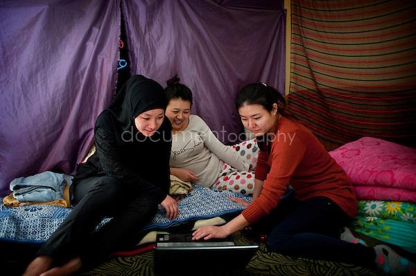 Copyright : Magali Corouge / Documentography.Le Caire, le 26 janvier 2013. .Yitong Shen dans la chambre de sa colocataire Jing Jing regarde, accompagnée de Jing Jing et de sa cousine Wenchao, une des dernières vidéos sur son ordinateur.