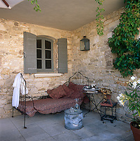 A wrought iron daybed and side table are placed on a covered paved terrace with stone walls on either side.
