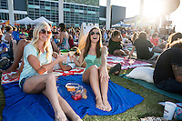 Two attractive females enjoy drinks at a weekly summertime outdoor live music and movie event in downtown Austin, Texas.
