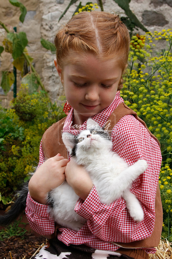 A young farm girl holding a kitten