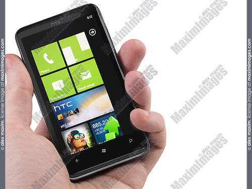 Hand with a Windows 7 phone. HTC HD7 smartphone with desktop tiles on its display isolated with clipping path on white background. High quality photo.