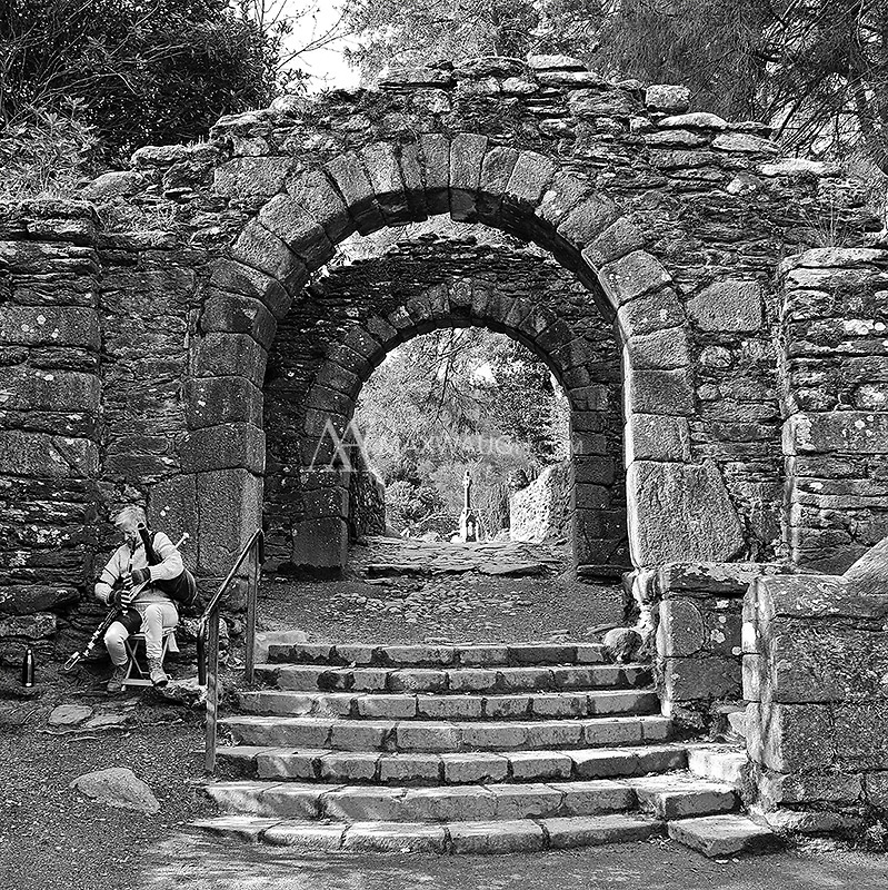 A musician plays Irish (Uillean) bagpipes at the entrance to the old cemetery at Glendalough.