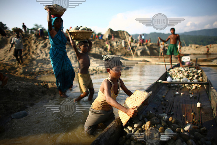 Children carry baskets of stones on their heads. At least 10,000 people, including 2,500 women and over 1,000 children, are engaged in stone and sand collection from the Bhollar Ghat on the banks of the Piyain river. Building materials such as stone and sand, and the cement which is made from it, are in short supply in Bangladesh, and commands a high price from building contractors. The average income is around 150 taka (less than 2 USD) a day.