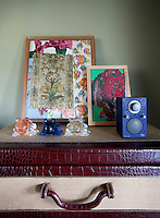 Three crystal frogs, some framed fabric swatches and a modern digital radio are displayed on an antique crocodile skin trunk