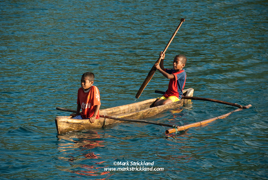Local kids paddle their Dugout canoe, Alor, Indonesia