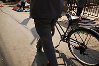Man in suit walks bicycle down street, Shanghai, China