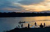 Xingu Indigenous Park, Mato Grosso State, Brazil. Aldeia Capivara (Kaiabi); children playing beside the river at sunset with a canoe on the river.