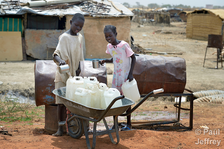 A boy and girl collect water in Abyei, a town at the center of the contested Abyei region along the border between Sudan and South Sudan. Homes here were looted and burned in 2011 when soldiers and militias from the northern Republic of Sudan swept through the area, chasing out more than 100,000 Dinka Ngok residents. A few thousand families have returned since northern combatants withdrew in 2012, yet their life is precarious. Although United Nations peacekeepers from Ethiopia today patrol the region, renewed attacks by northern-backed Misseriya militias in 2013 have many worried. The African Union has proposed a new peace plan, including a referendum to be held in October 2013, but it has been rejected by the Misseriya and Khartoum. The UN mission here also provides water to these roadside containers from which residents can obtain safe drinking water. The town's wells were destroyed by the northern combatants before they left in 2012.