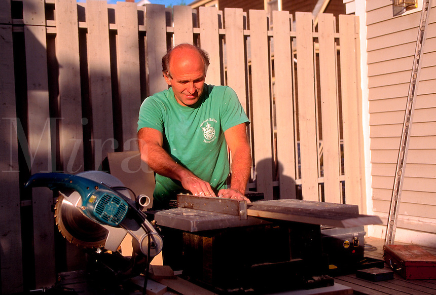 Carpenter using a table saw outdoors.