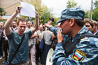 17/08/2012, Moscow, Russia..A policeman gestures at a protester waving a blank sign outside the court as Maria Alyokhina, Yekaterina Samutsevich and Nadezhda Tolokonnikova of punk band Pussy Riot are sentenced to two years prison for their performance in the Christ The Saviour Cathedral.