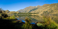 Panoramic Photo of Early Morning Reflections at Lake Moke, Queenstown, South Island, New Zealand. Lake Moke, 10km from Queenstown is both a stunning lake and a department of conservation campsite (DOC campsite) with access for both caravans and campervans. In the early mornings Lake Moke is often perfectly still providing picture perfect reflections of the surrounding hills and mountains in the water. The combination of a fabulous golden hour as the sun rose over the hills, the morning mist lifting from the lake, and the rich, orange, autumn trees made this nights camping at the Lake Moke department of conservation campsite (DOC campsite) particularly special.