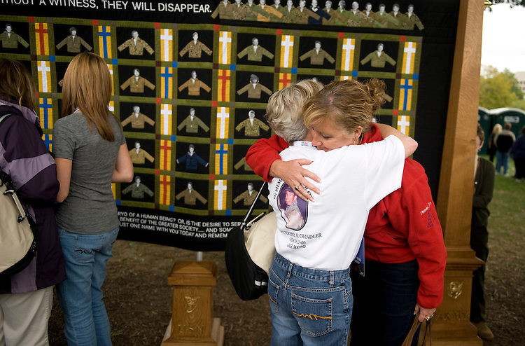 Debbie Lee, right, who lost her Marc Alan Lee, a Navy SEAL killed in Iraq, hugs Jonnie Chandler, who lost her son Capt. Jeremy Chandler, an Army Special Forces officer killed in Afghanistan, during a ceremony on the West Lawn which was part of the Weekend of Remembrance to honor fallen Iraq and Afghanistan service members on Saturday, Sept. 26, 2009.  Behind them is the Lost Heroes Art Quilt created by Julie Feingold which honors those who have been killed.